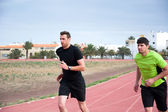 Two men running on running track — Stockfoto
