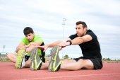 Men stretching in running track — Stockfoto
