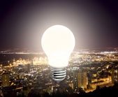 The burning light bulb on the background lights of the night cit — Stockfoto