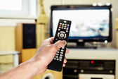Men's hand sends the remote control on the TV  — Stock Photo