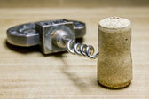 Corkscrew and Cork from wine on a wooden surface — Stock Photo