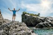 Man arms outstretched standing on a rock by the sea — Stock Photo