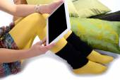 Digital tablet on the legs of a young woman — Foto Stock