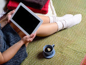 Digital tablet on the legs of a young woman — Stockfoto