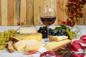 Different Savoie cheeses with a glass of red wine — Stock Photo