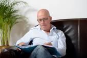 A senior man sitting in a sofa taking notes — Foto de Stock