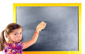 A little girl with pigtails writes on a blackboard — Stock Photo
