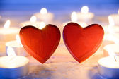 Small red wooden hearts and candles — Stock Photo