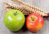 Apples and wheat cobs placed on a wooden table — Stock Photo