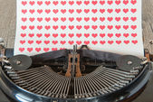 Old typewriter with red hearts on paper — Stock Photo