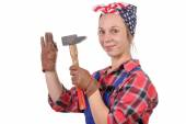 Young woman handyman drive a nail with a hammer — Stock Photo