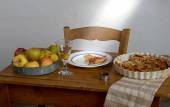 Apple pie on a table with apples — Stock Photo