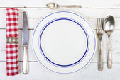 Plate with silver cutlery on an old white table — Stock Photo