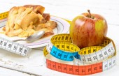 A pastry and apple with  a measuring tape — Stock Photo