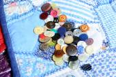 Lot of buttons placed on a quilting  — Stock Photo