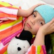 A little girl in her bed has a headache — Stock Photo #70929849