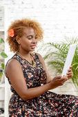 En ganska ung svart kvinna med rött hår ser en digital tabell — Stockfoto