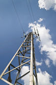 Electricity high voltage pole and the blue and cloudy sky — Stock Photo