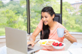 Woman with breakfast using laptop — Foto de Stock