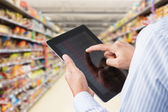 Businessman checking inventory in minimart on touchscreen tablet — Stock Photo