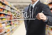 Business man writing word retail in the supermarket — Stock Photo