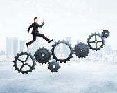 Businessman runs on gears — Stock Photo