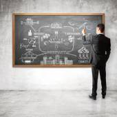 Businessman drawing scheme  on chalk board — Stock Photo