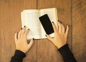 Flicka med mobiltelefon och bok — Stockfoto