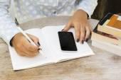 Flicka skriver i anteckningsboken med mobiltelefon — Stockfoto