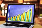 Laptop met zakelijke grafiek op een houten tafel — Stockfoto