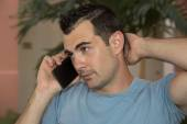 Dark haired male model in stressful cell phone conversation — Stock Photo