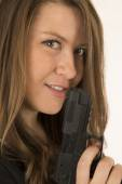 Close-up portrait of a woman holding a pistol with a smirk on he — Foto Stock