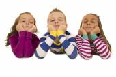 Beautiful young children wearing pajamas leaning on elbows — Stock Photo