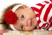 Cute newborn girl laying down with flower headband — Stock Photo
