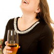 Fun young woman holding a wine glass looking up laughing — Stock Photo #65483063