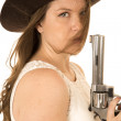 Serious cowgirl holding a pistol with her hair in her face — Stock Photo #66844765