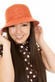 Beautiful smiling teen girl model adjusting orange hat — Photo
