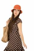 Daydreaming teen female model wearing a brown polka dot dress an — Stock Photo