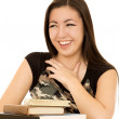 Young girl sitting behind a pile of books laughing — Stock Photo #69949197