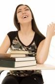 Gülüyor kitaplarla dolu masa başında oturan kız öğrenci — Stok fotoğraf