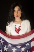 Beautiful woman with her lips puckered holding stars and stripes — Stock Photo