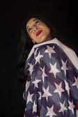 Jolie femme avec drapeau américain levant fond noir — Photo