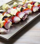 Raw vegetables skewer on a plate over wooden background — Stock Photo