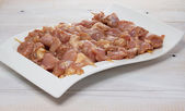 Raw skewer meat on a white plate over wooden background — Stock Photo