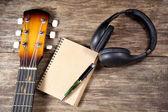 Headphone guitar notebook pencil — Stock Photo