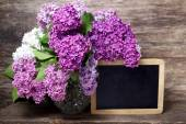 Lilac flowers in a vase and blackboard — Stock Photo