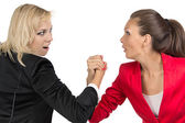 Arm wrestling of two smiling businesswoman — Stock Photo