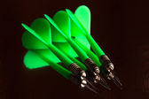 Small group of green darts and it reflection — Stockfoto
