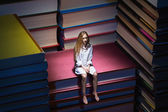 Small young woman sitting on books — Photo