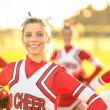 Portrait of an happy young cheerleader in action outdoors - Group of girlfriends during cheerleading sport training at high school — Stock Photo #52782497
